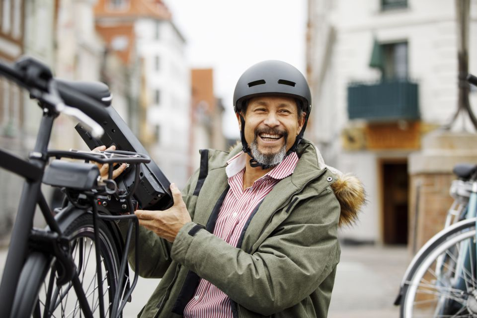 Senior man changing battery on electric bicycle