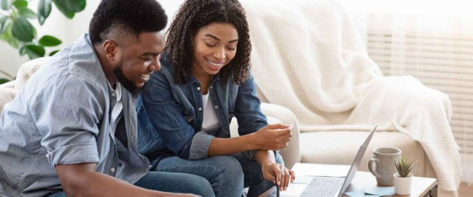 Household Budget. Smiling Black Couple Discussing Total Amount Of Their Spends At Home, Happy About Wise Planning