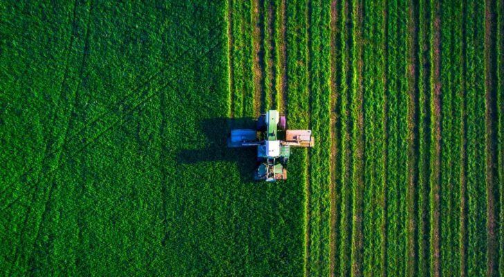 a tractor cultivating a farm from an aerial view