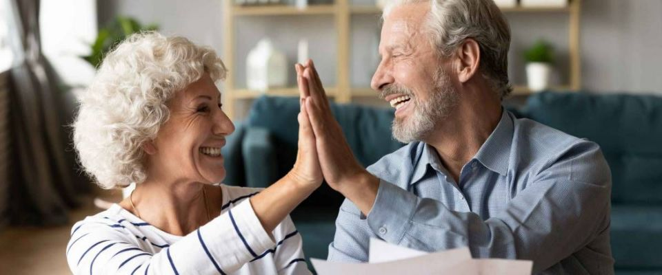 Excited older couple giving high five, mature family celebrating success, checking or paying domestic bills, planning budget, smiling mature man holding financial documents, reading good news