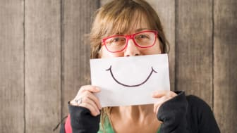 A woman holds a drawing of a smile in front of her mouth