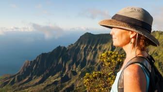 A woman enjoys a view while hiking.