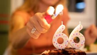 Lighting a No. 66 birthday candle on a cake.