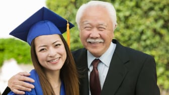 Grandfather hugging granddaughter wearing college graduation cap and gown