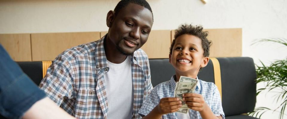 Father and son sitting together son hold american bills currency