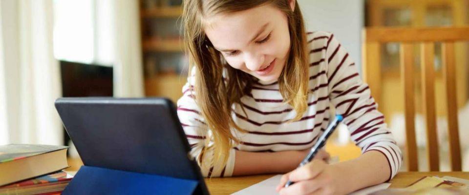Preteen schoolgirl doing her homework with digital tablet at home.