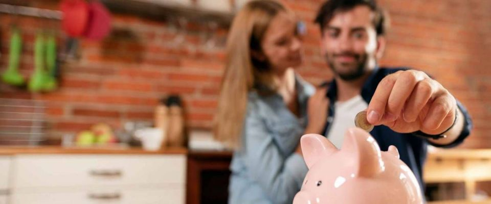 Happy couple inserting coin in piggybank. Home budget, family finance concept. Wide photo with space for your text