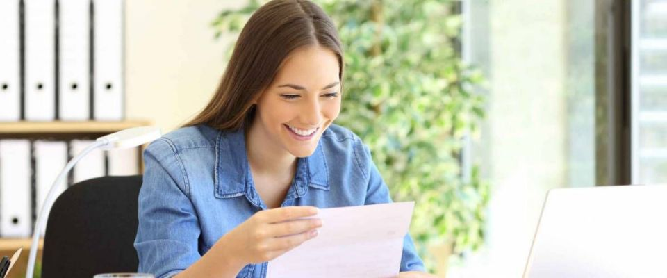 Happy entrepreneur woman reading good news in a letter in a desk at office