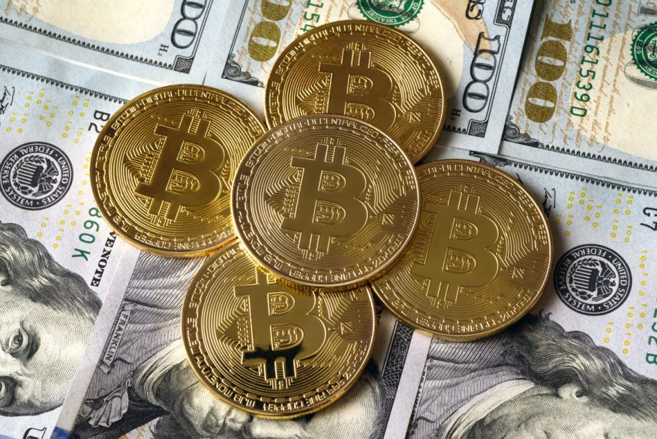 UKRAINE - 2020/12/06: In this photo illustration the Bitcoin cryptocurrency commemorative coins seen on top of the USA Dollars notes. (Photo Illustration by Mykola Tys/SOPA Images/LightRocket via Getty Images)
