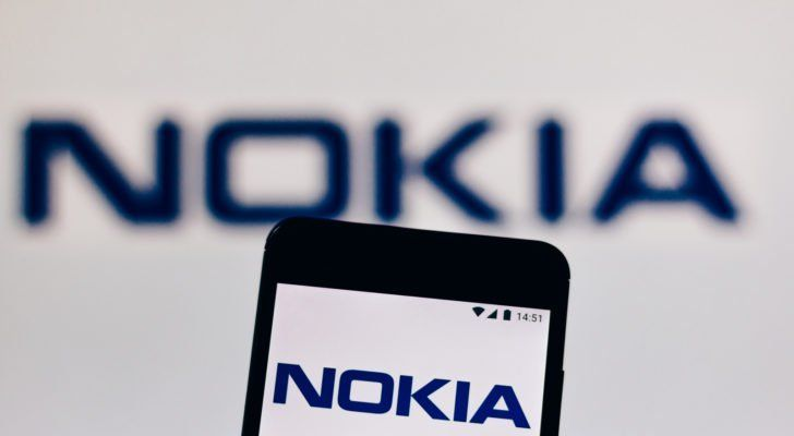 a backdrop featuring the Nokia (NOK) logo with a mobile phone featuring the Nokia logo on its screen in the foreground